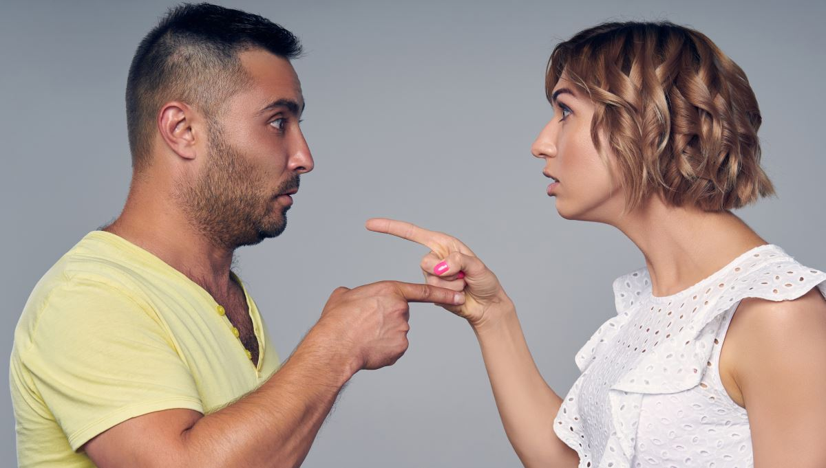 couple facing each other, upset, pointing a finger at each other
