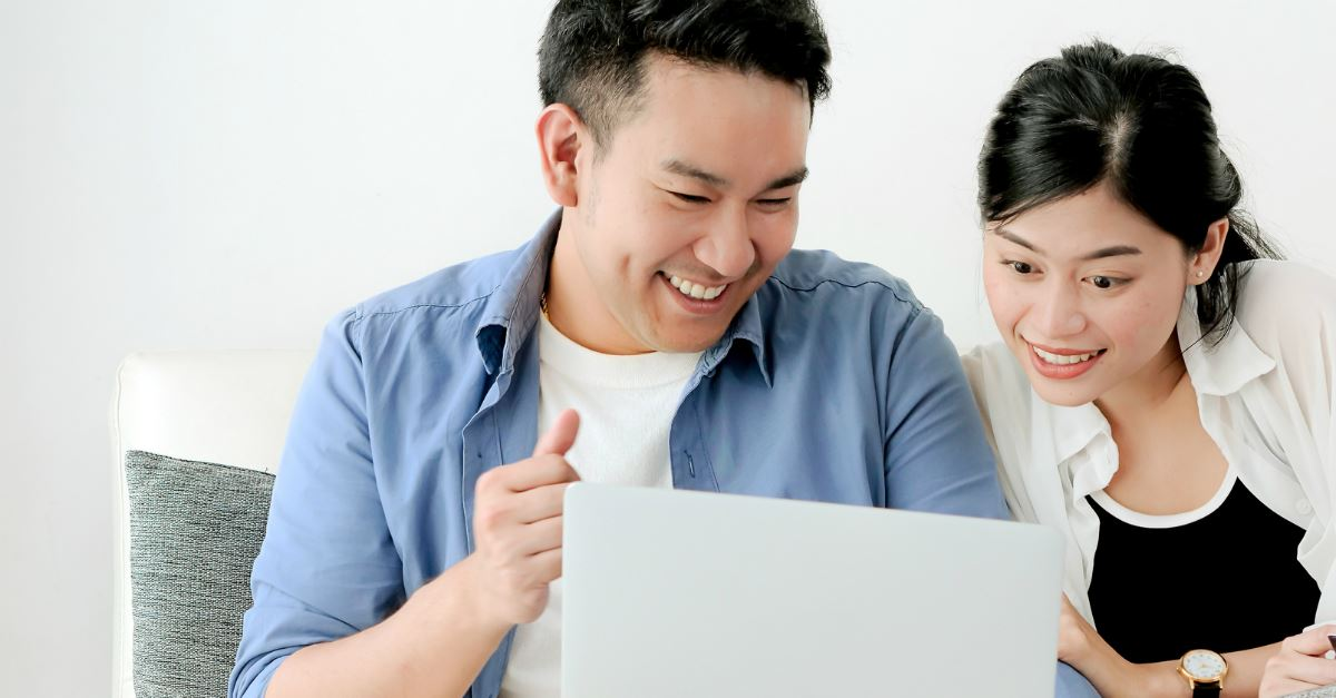 asian couple smiling together and looking into laptop screen