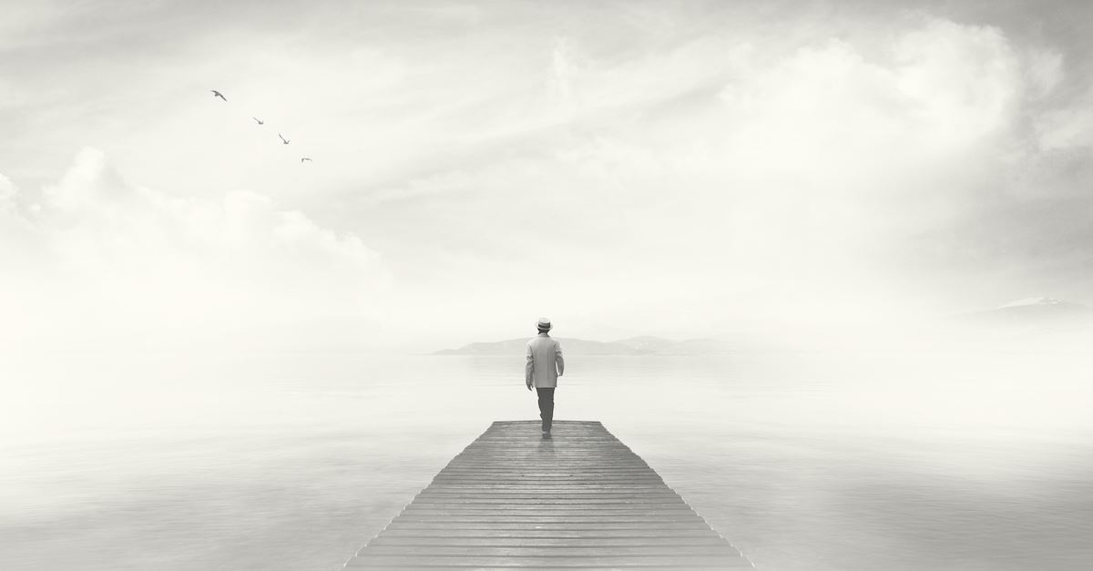 man walking on gray bridge with gray background, depression