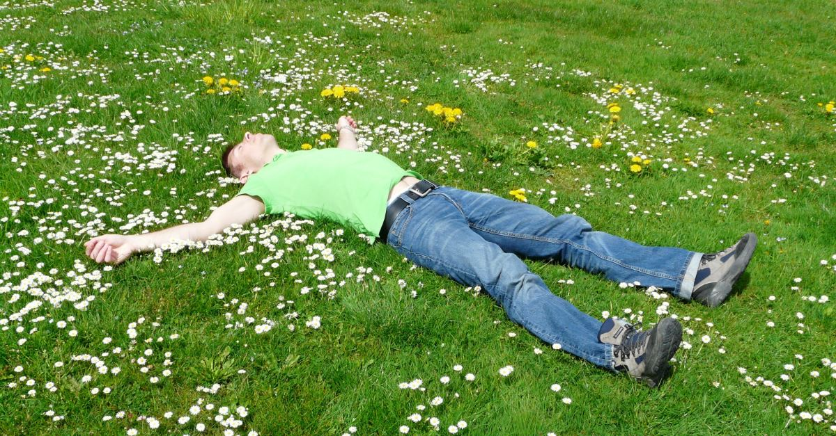 man laying in field of flowers, arms outstretched, sleeping