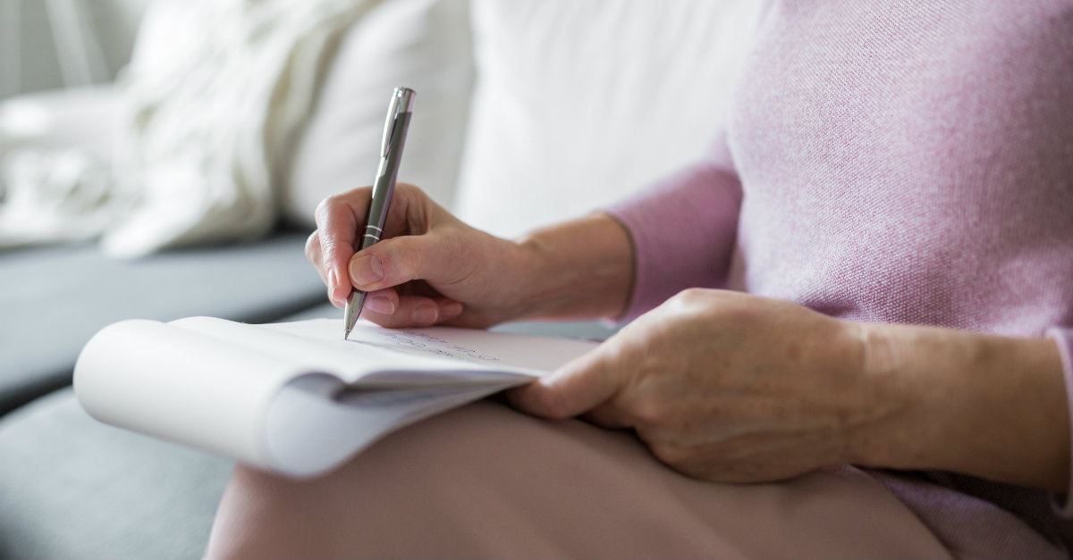 woman writing on a notepad