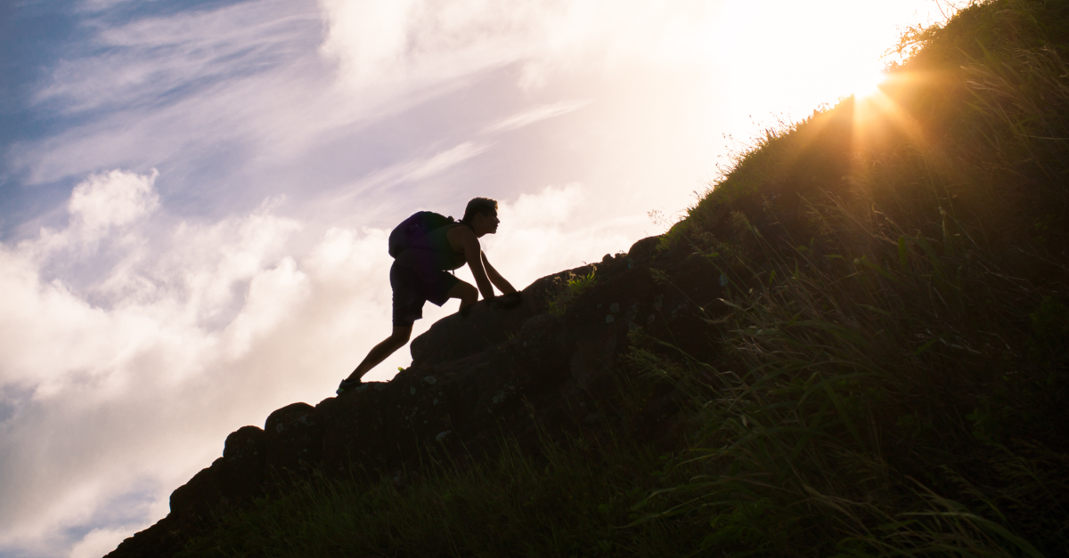 silhouette of a man climbing a hill toward the sun