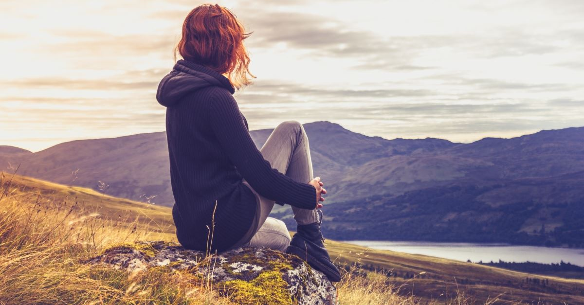 a woman sitting and looking at mountains, a meditation prayer