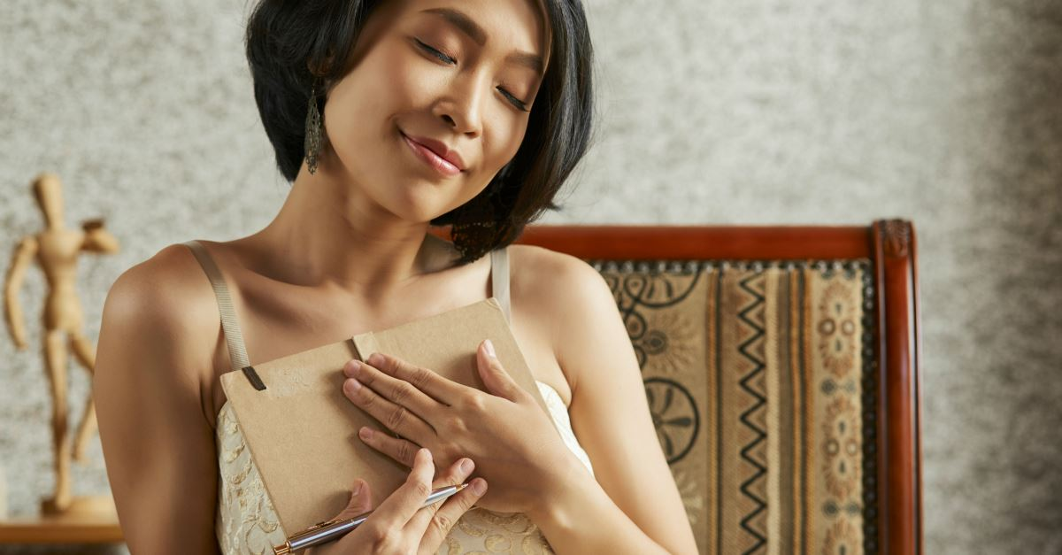 asian woman smiling with eyes closed restful holding journal to chest