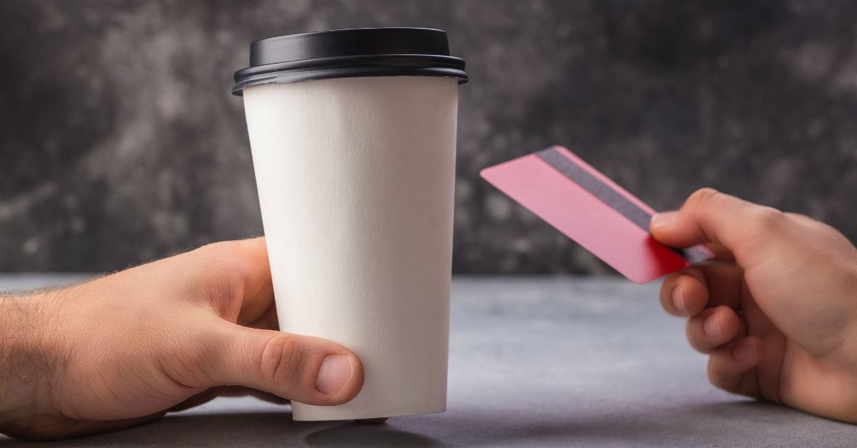 man's hand holding disposable coffee cup, girl's hand holding credit card