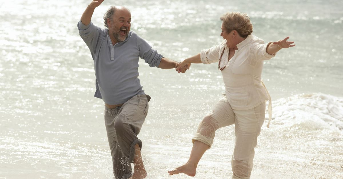 older couple holding hands and happily kicking up their feet splashing in water at shoreline