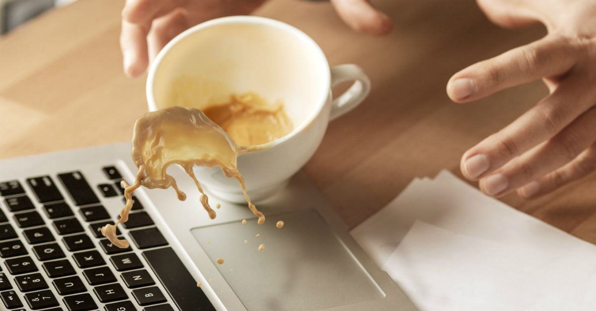 hands trying to grab spilling coffee cup splashing coffee on laptop