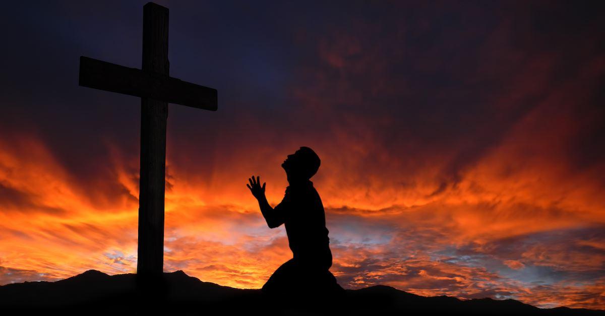 man praying at cross at sunset, grief