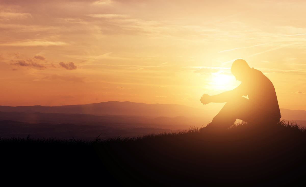 sunset silhouette of man sitting with head bowed, praying