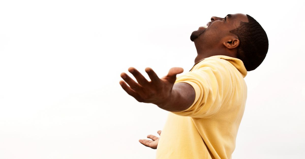 man with arms out wide, smiling, head back towards sky in praise