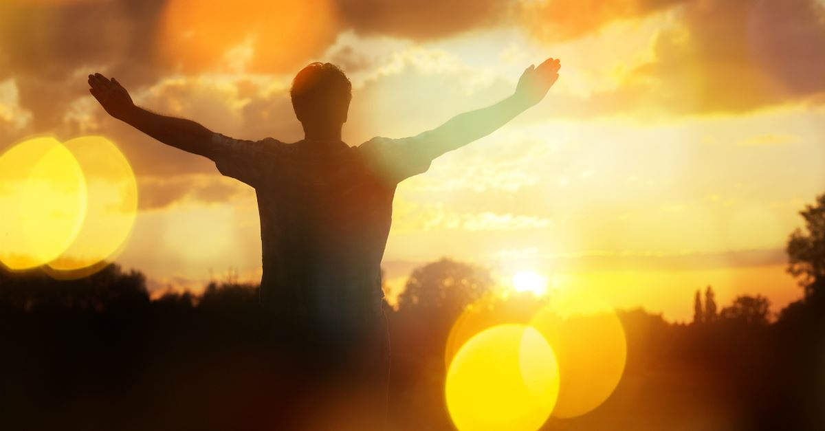 backview of man with arms outstretched in praise in golden sunrise