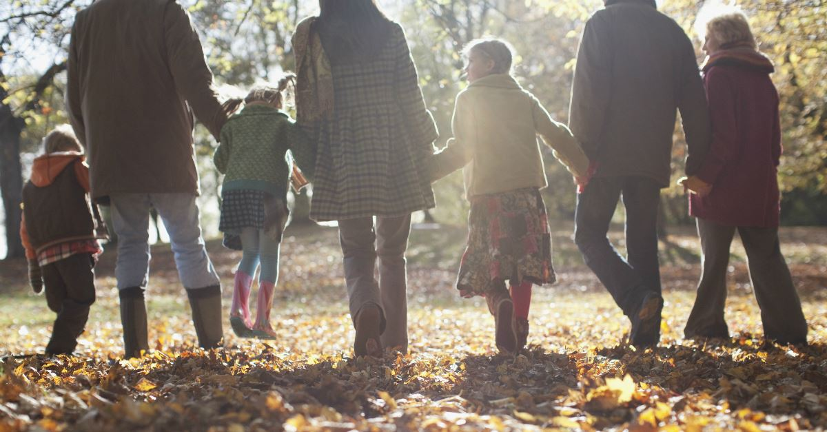 back view of extended family walking through fall leaves