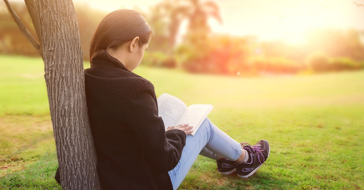 young girl reading outside by tree, quotes for teens