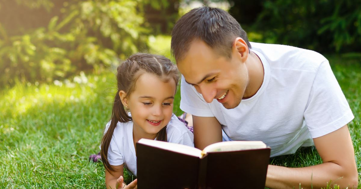 father and daughter reading Bible on lawn, kids and theology