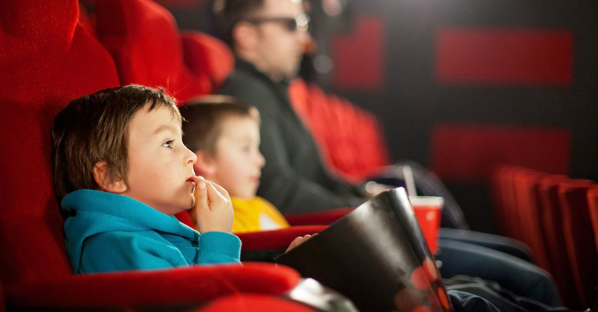 children sitting in movie theater eating popcorn