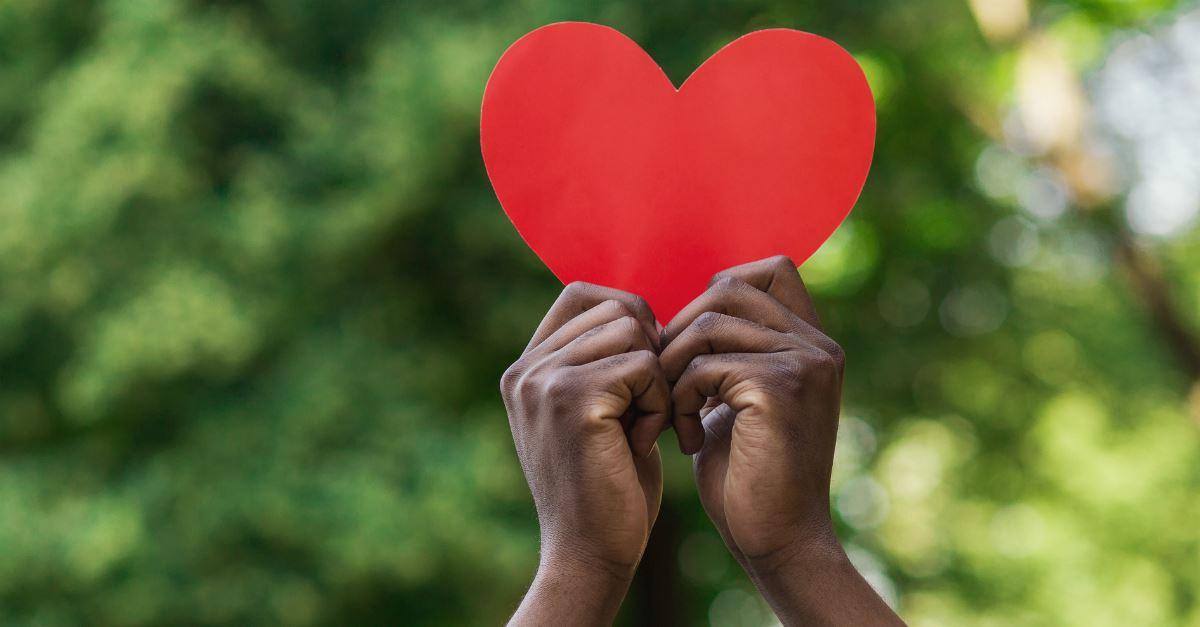 tween kids' hands holding up red paper heart