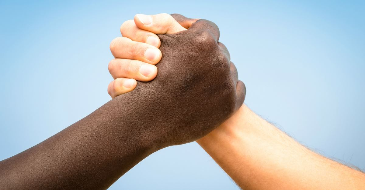 hand and forearm of a black and white person grasping hands together