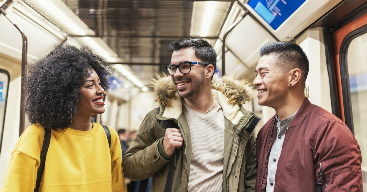 group of adults of various ethnicities on subway smiling at each other
