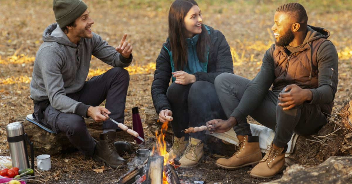 adult friends enjoying roasting hot dogs over a campfire