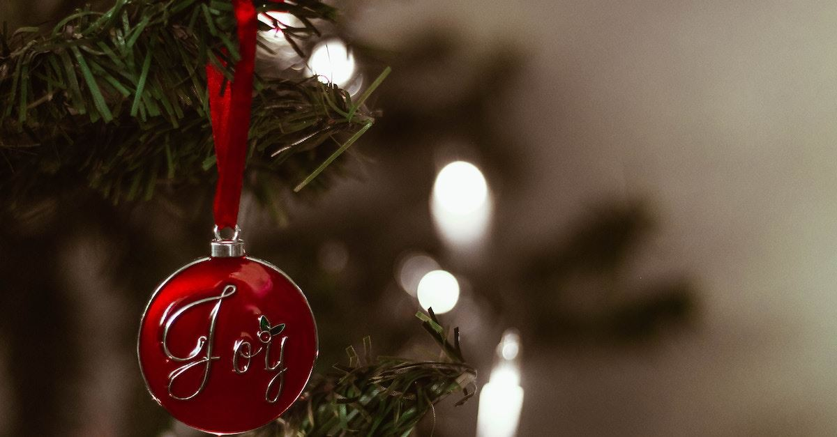 joy Christmas ornament hanging on Christmas tree, meaningful Christmas