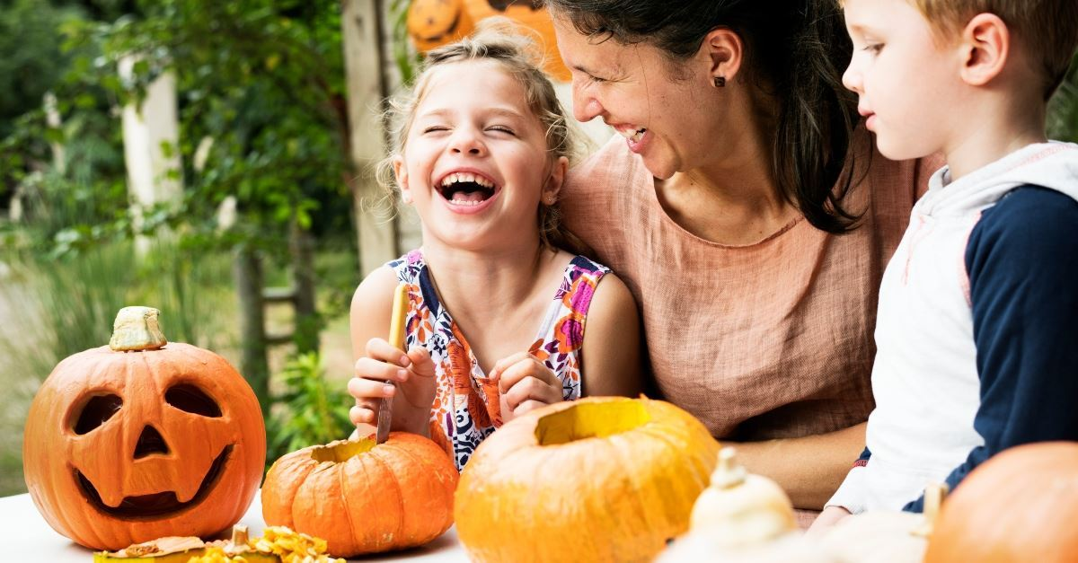 Children and their mother laugh as they carve pumpkins for Halloween