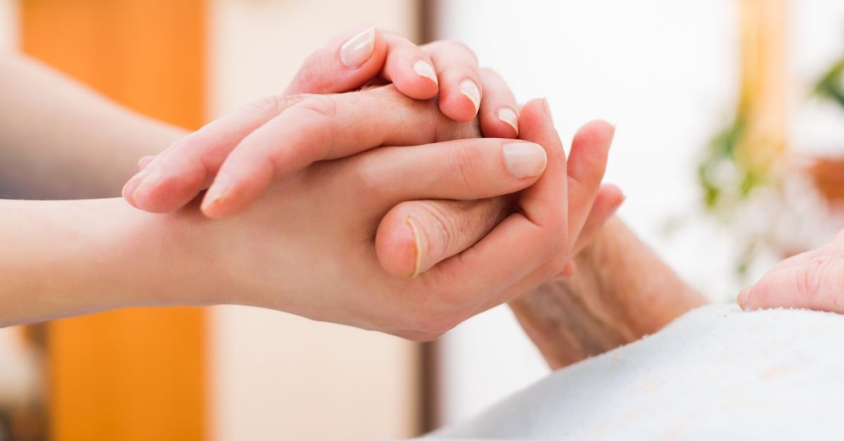woman holding the hand of a sick person in the hospital