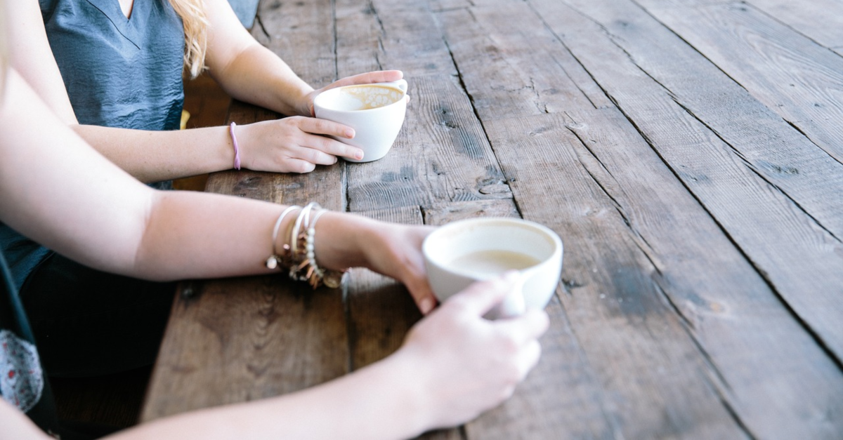 women sitting and visiting over coffee