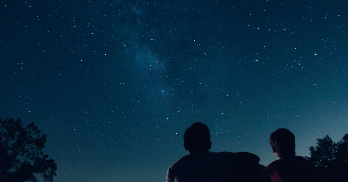 two people looking at starts night sky