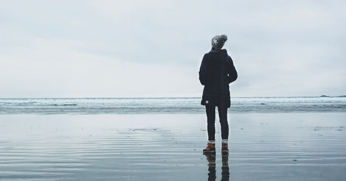 back of woman winter clothes standing in front of ocean, how to be still in restless culture
