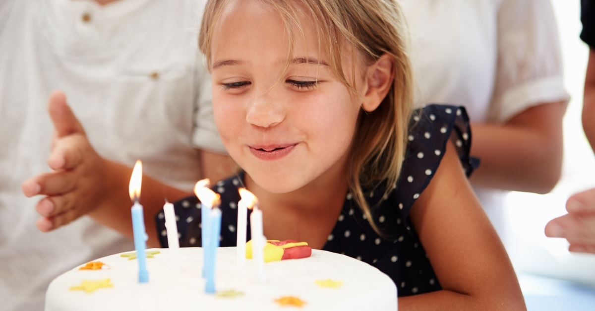 little girl blowing out birthday candles on cake