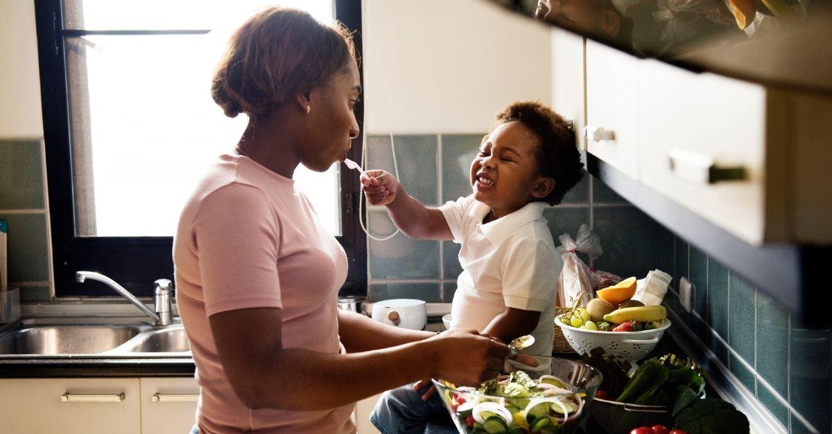 child feeding mom smiling sitting on kitchen counter, redefining organization