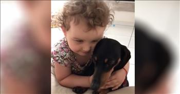 Little Girl Snuggles With Puppy
