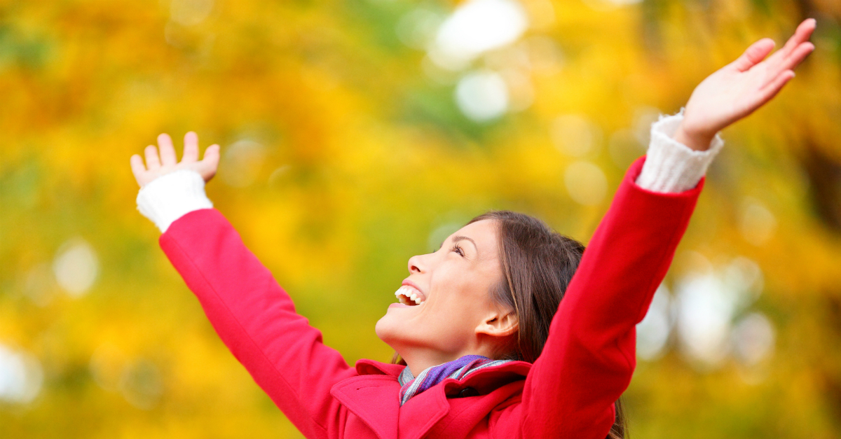 woman in autumn outdoors, arms up in praise, enter his courts with thanksgiving