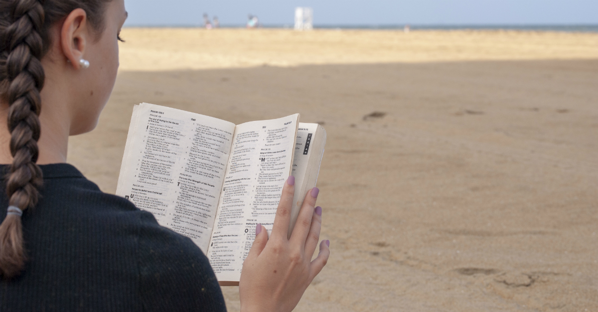 Young woman reading the Bible on the beach