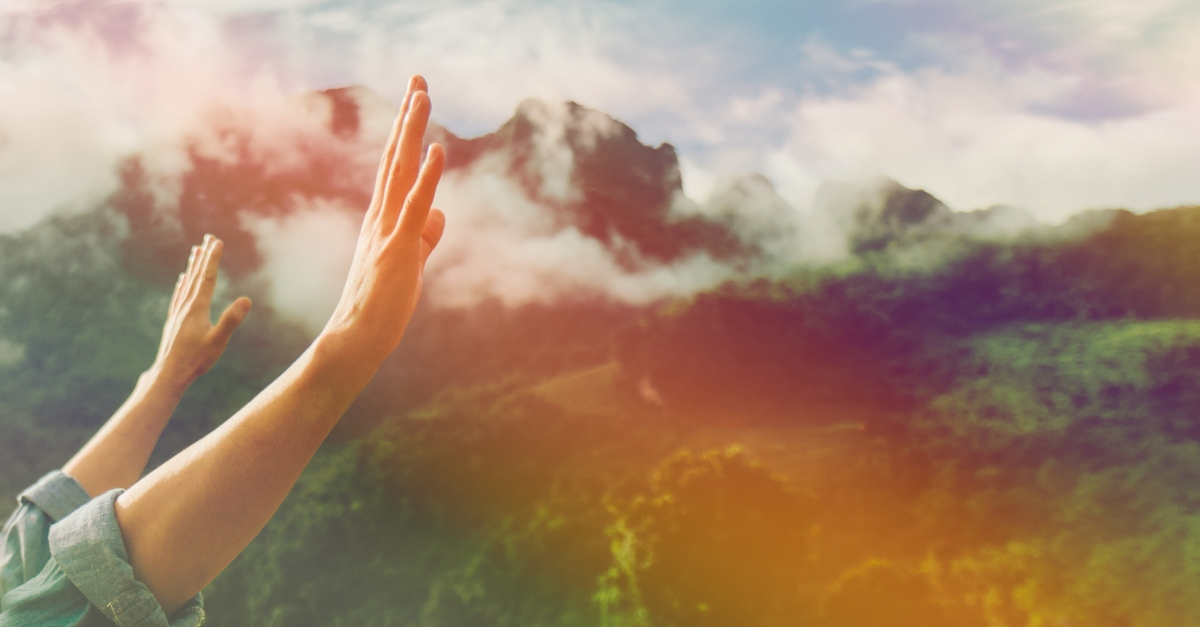 hands raised in worship with nature background rainbow, collective prayer for healing from chronicles