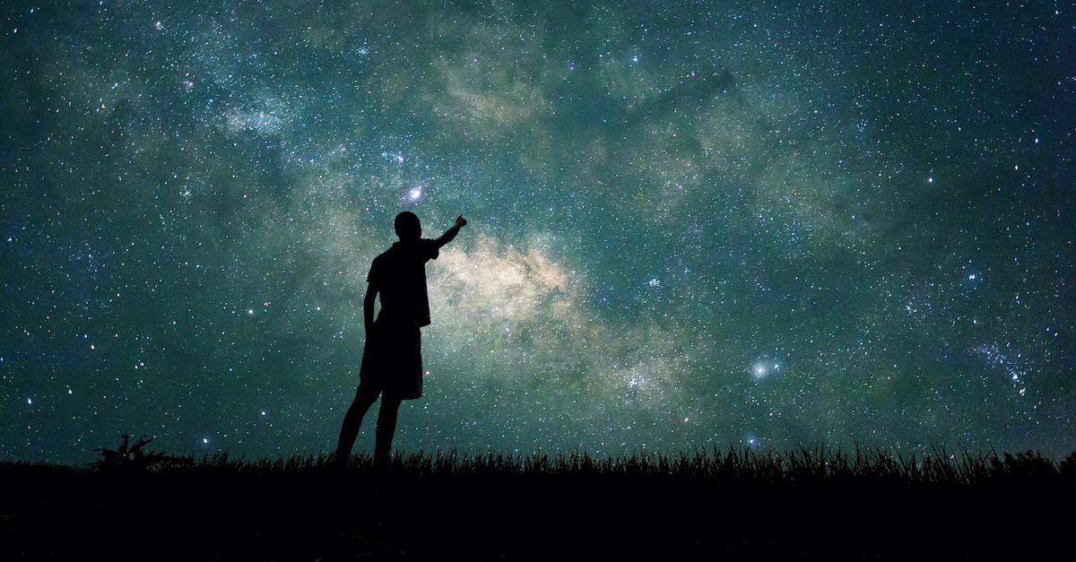silhouette of man pointing at stars in the nigh sky, how old is the earth?