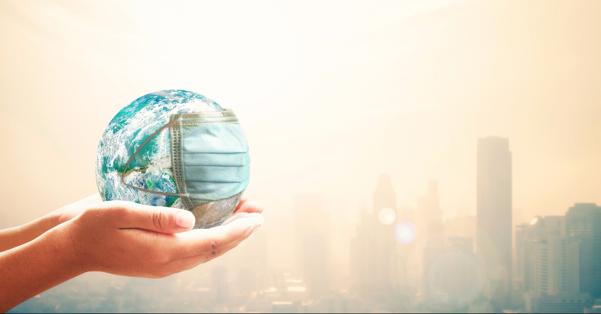 Hands holding a globe with a mask on it, over a city skyline