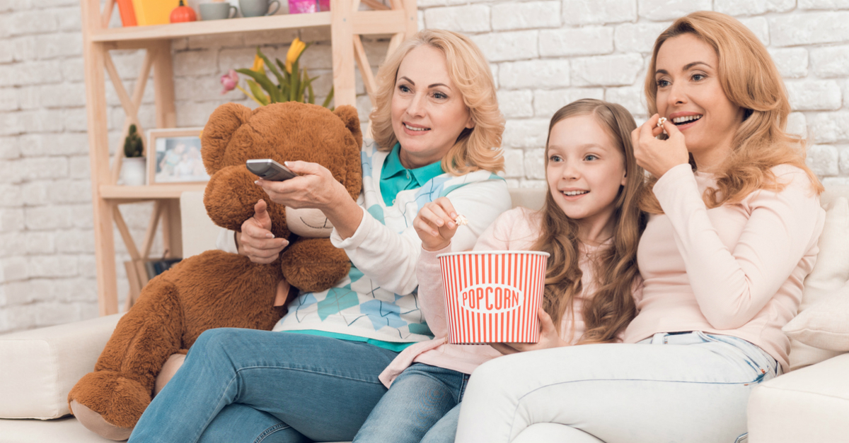 mom adult daughter or daughter-in-law and granddaughter watching movie