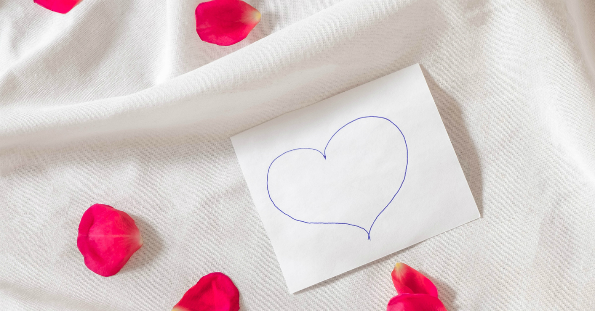 rose petals on white fabric love note heart