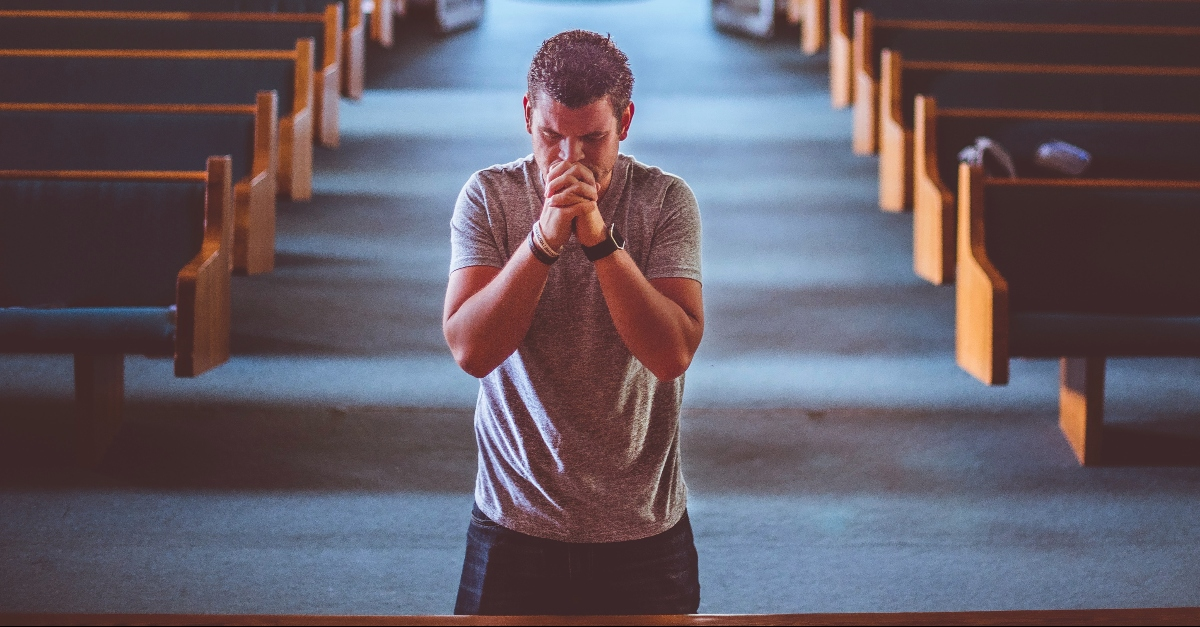 Man kneeling at the altar of a church