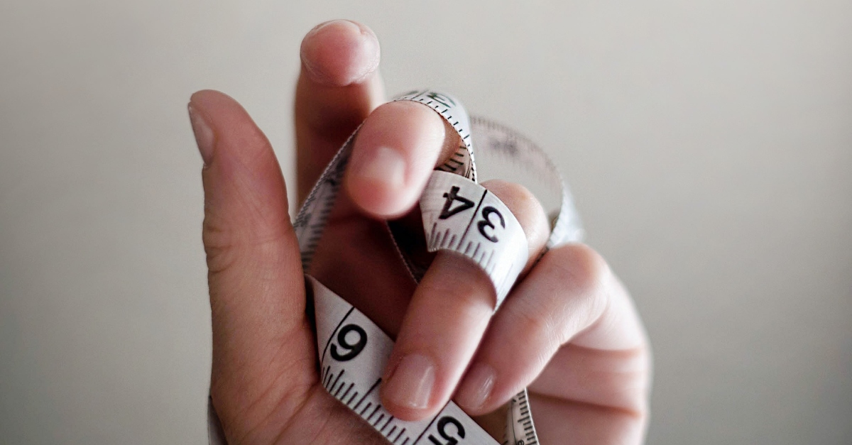 close-up of hand holding measuring tape
