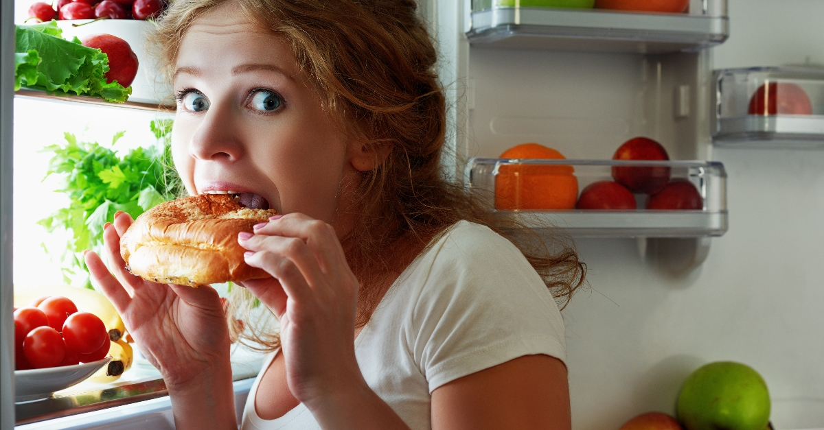 woman looking guilty eating snack from refrigerator late at night
