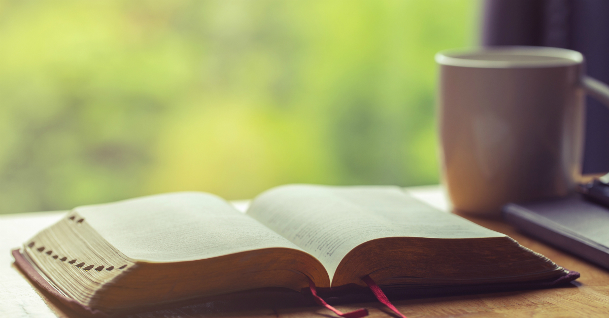 open bible next to coffee on table outdoors