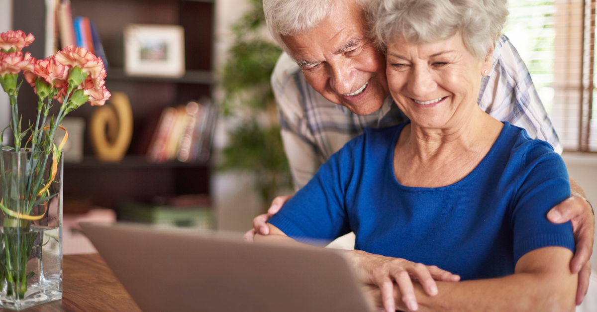elderly couple smiling into laptop computer virtual technology