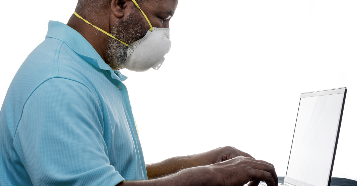 elderly man with face mask on at laptop computer