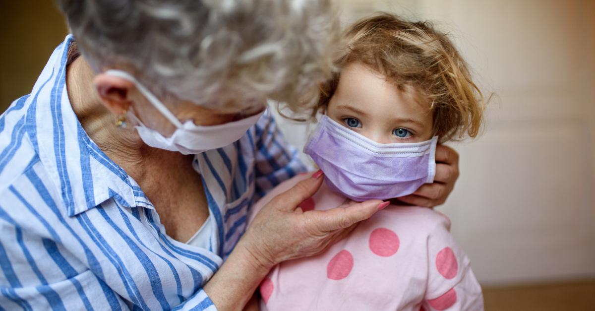 senior woman grandmother putting face mask on granddaughter coronavirus