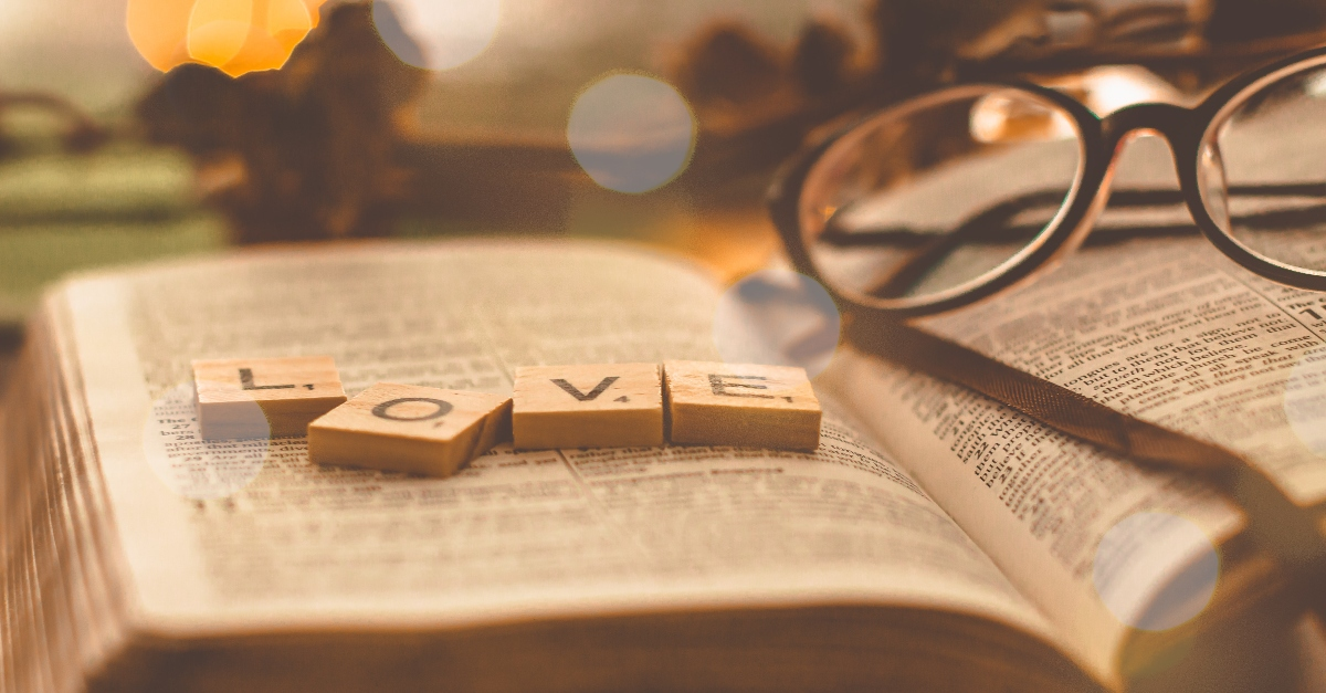 Bible opened with scrabble pieces that say love and Glasses on it