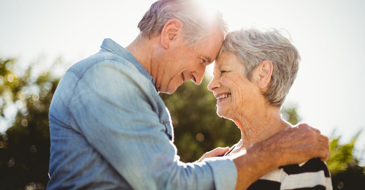 senior adults facing each other hug at sunset happy, prayer intercession for spouse's health