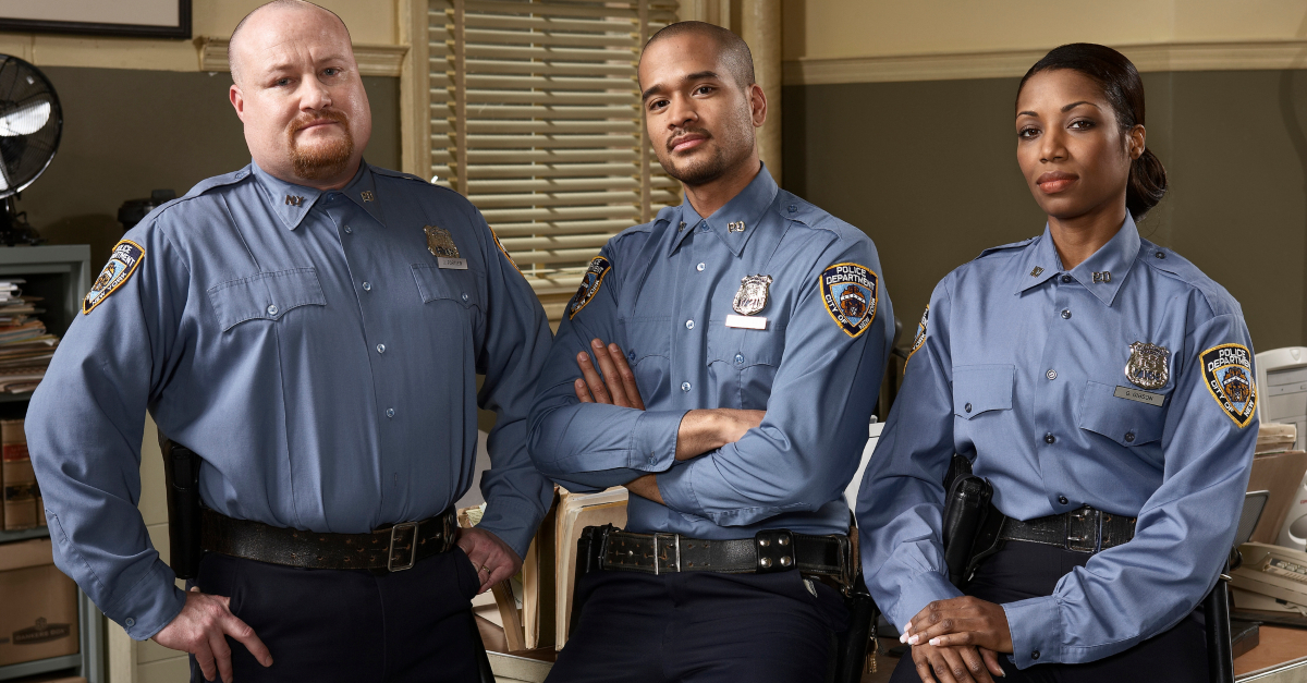 three police officers in uniform in office