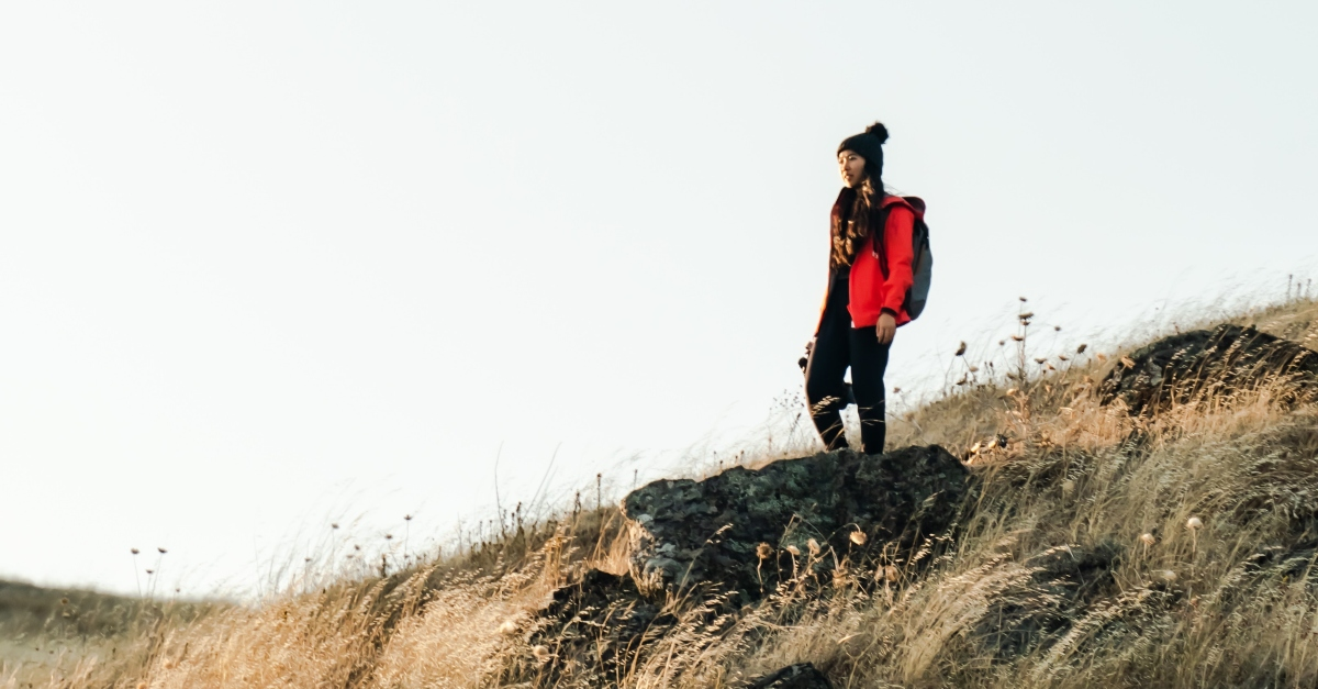 woman hiker standing on golden hill of grass looking forward, when you're afraid of falling behind